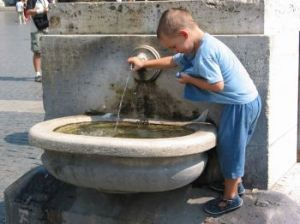 A boy at a fountain in St. Peter's Square.