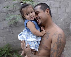 Henri Aguilar, a former gang member, holds his 1-year-old daughter, Genesis, in the yard of his home in Chamelecon, Honduras, May 2, 2007. Aguilar, who was a member of one of Honduras\' most notorious gangs, was assassinated by three masked men five days later. Under the guidance of Maryknoll Father Thomas Goekler, he had left the gang and was married, working full time and heavily involved in parish life. (CNS/Paul Jeffrey)