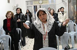 Iraqi refugee Sabria Yousef Nona prays during Mass in the Chaldean Catholic Vicariate in Amman, Jordan, Feb. 14, 2007. A sole Chaldean priest in Amman looks after the spiritual needs of 8,000-10,000 Catholics, including many refugees from Iraq. (CNS/Debbie Hill)
