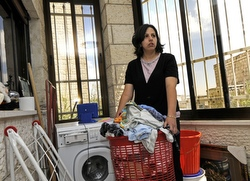 Wafa Shatleh, 34, carries clothes to store in her laundry room until her family receives running water so she can wash them in Beit Jalla, West Bank, July 29. (CNS/Debbie Hill)