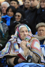 An elderly woman guards herself against the cold at a Mass in Lourdes, France, last February for the feast of Our Lady of Lourdes. (CNS/Nancy Wiechec)