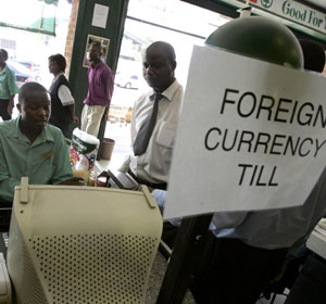 A foreign currency sign is seen as shoppers buy products at a supermarket in Harare, Zimbabwe. The Zimbabwean government recently allowed food outlets to accept foreign currency in order to tackle the increasing inflation. (CNS/Reuters)