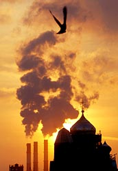 A cathedral is seen silhouetted against the sunset in St. Petersburg, Russia, as smoke rises in this 2005 file photo. (CNS/Reuters)
