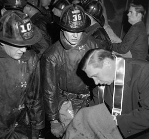 A priest blesses a deceased child after the Dec. 1, 1958, fire at Our Lady of the Angels School in Chicago. (CNS/Catholic New World)