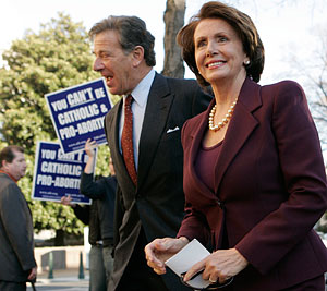 Rep. Nancy Pelosi, the new speaker of the House, arrives with her husband, Paul, at an interfaith service for members of Congress at St. Peter's Catholic Church near the Capitol in Washington Jan. 4. A handful of protesters from the American Life League held signs outside the church.