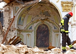 A fireman surveys a damaged church in St. Gregorio near L'Aquila. (CNS photo/Max Rossi, Reuters)