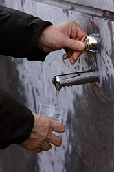 MAN FILLS GLASS WITH WATER FROM SPRING IN LOURDES