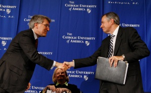 Professors Robert George, left, and Douglas Kmiec shake hands at the conclusion of a discussion at the National Press Club in Washington May 28. The discussion was moderated by professor Mary Ann Glendon, center, the former U.S. ambassador to the Vatican . (CNS/Paul Haring)