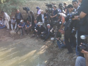 Photographers await the pope at the Jordan River