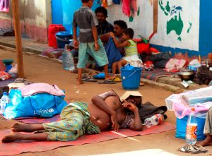 A man rests on a mat as other Tamil civilians and their children sit near their belongings in a refugee camp located on the outskirts of the town of Vavuniya in northern Sri Lanka May 4. (CNS photo/Reuters)