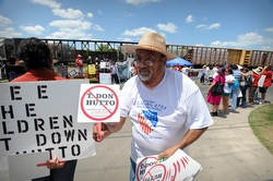 Jose Orta hands out fans during a vigil at the T. Don Hutto Family Residential Facility in late June in Taylor, Texas. The former medium security prison converted for family detention in 2006, has been the subject of harsh criticism from attorneys, immigrant advocates and civil rights organizations. (CNS/Bahram Mark Sobhani)