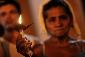 A Catholic woman participates in a recent candlelight vigil in San Pedro Sula, Honduras, protesting the coup that ousted Honduran President Manuel Zelaya. (CNS photo/Daniel LeClair, Reuters)