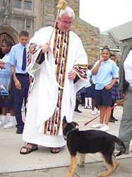 Capuchin Franciscan Father Paul Zaborowski, pastor of St. Ambrose Church in Baltimore, blesses 3-month-old German shepherd puppy Maximus during the blessing of the animals in 2007. (CNS/Chaz Muth, Catholic Review)
