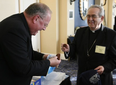 Archbishop Timothy M. Dolan of New York shares a Tastykake with Cardinal Justin Rigali of Philadelphia during a break at the U.S. Conference of Catholic Bishops' fall meeting in Baltimore Nov. 16. The two presented each other with T-shirts after making g ood on a wager after the Yankees won their 27th World Series. (CNS/Bob Roller)