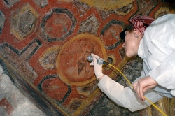 Restorer uses a laser on the image of St. Paul in the Catacomb of St. Thecla. (Pontifical Commission for Sacred Archaeology)