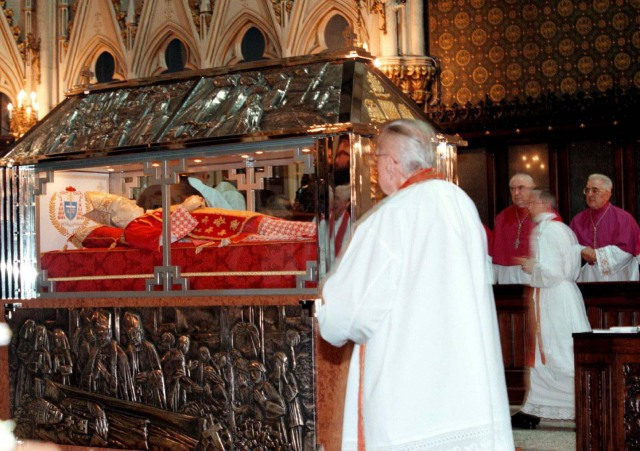 Priests pray around the glass sarcophagus of Cardinal Aloysius Stepinac in the cathedral of Zagreb. (file photo Oct. 1998)
