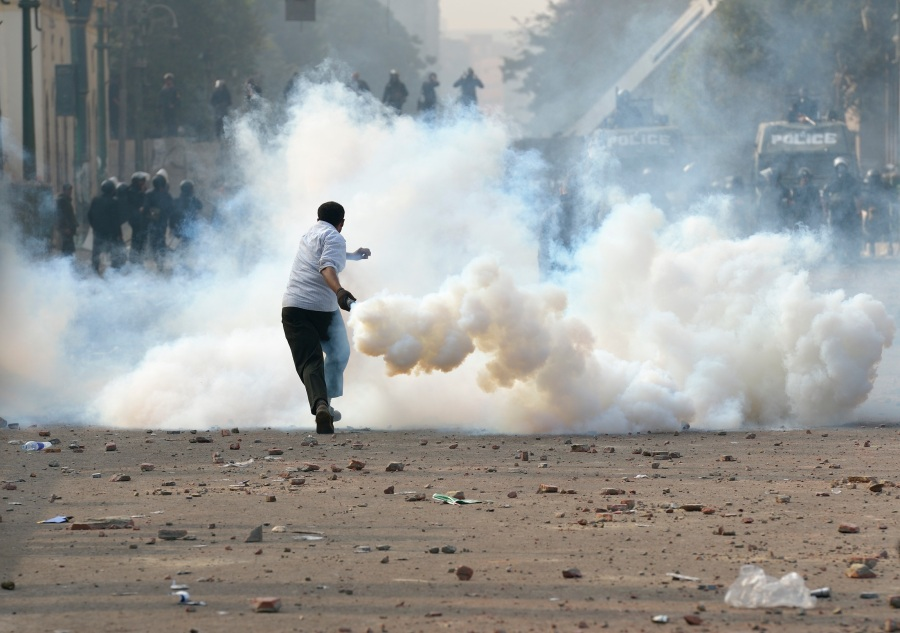 A demonstrator prepares to throw a smoking tear gas canister back at police during Nov. 25 protests in and around Tahrir Square in Cairo. (CNS photo/Paul Jeffrey)