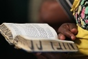 A woman uses a hand missal  in Swahili during Mass in Kenya. (CNS Photo/Nancy Wiechec)