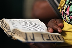 A woman uses a hand missal in Swahili during a Mass in Kenya. (CNS Photo/Nancy Wiechec)