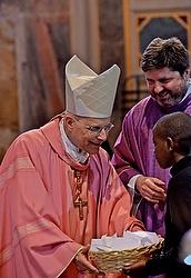 Cardinal George receives a basked of hand-written prayers. (CNS/ Chris Warde-Jones)