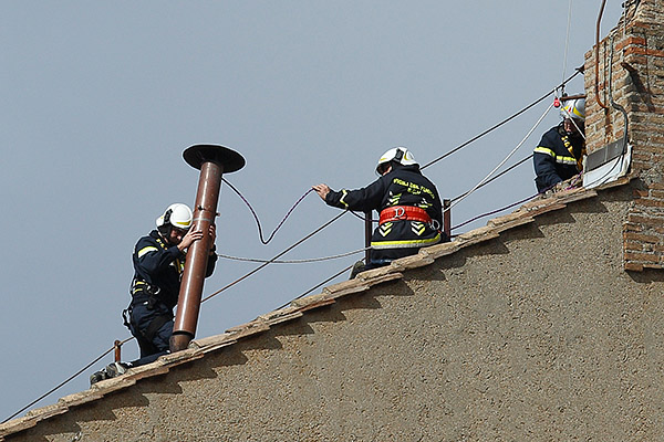 Vatican firefighters put the chimney in place this morning. (CNS/Paul Haring)