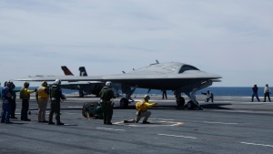 Crew prepares to launch pilot-less drone combat aircraft from aircraft carrier in Atlantic Ocean off coast of Virginia May 14. (CNS/Reuters)