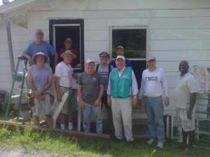 Father George Kloster, wearing vest, is pictured with a group of volunteers from his parish and others in 2012 as they repaired a home damaged by a tornado in Murphy, N.C. (Courtesy Catholic News Herald)
