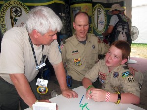 At session on rosary making, Ed Martin, national chairman of the National Catholic Committee on Scouting instructs Stephen Kiss of Troop 461, from St. Jane Frances de Chantel Parish in Washington Archdiocese. (Photo courtesy of Msgr. John B. Brady)