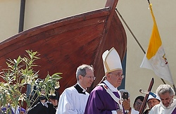 Pope walks past a boat as he arrives for Mass yesterday in Lampedusa. (CNS/Paul Haring)