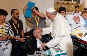 Pope Francis blesses a sick man as a man with a blue iPad captures the moment in the Basilica of Our Lady of Bonaria. (CNS photo/Paul Haring)