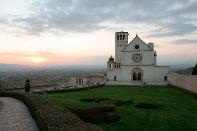 SUN SETS NEAR BASILICA IN ASSISI, ITALY