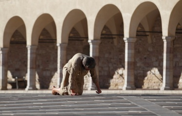 BAREFOOTED PILGRIM APPROACHES BASILICA OF ST. FRANCIS IN ASSISI