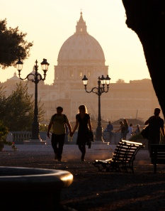 DOME OF ST. PETER'S BASILICA SEEN AS COUPLE STROLLS IN EVENING