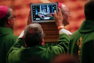 Priest takes photo with tablet as Pope Francis celebrates Mass in St. Peter's Basilica