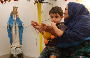 WOMAN PRAYS ROSARY NEAR STATUE OF MARY AT HOME IN IRAQ