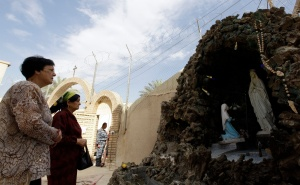 WOMEN PRAY NEAR STATUE OF MARY DURING EASTER MASS OUTSIDE CATHOLIC CHURCH IN IRAQ