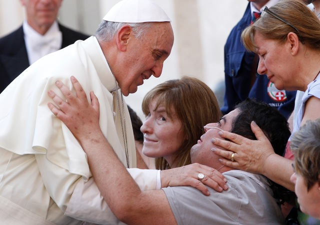 Pope greets man with disability after Mass in St. Peter's Square at Vatican