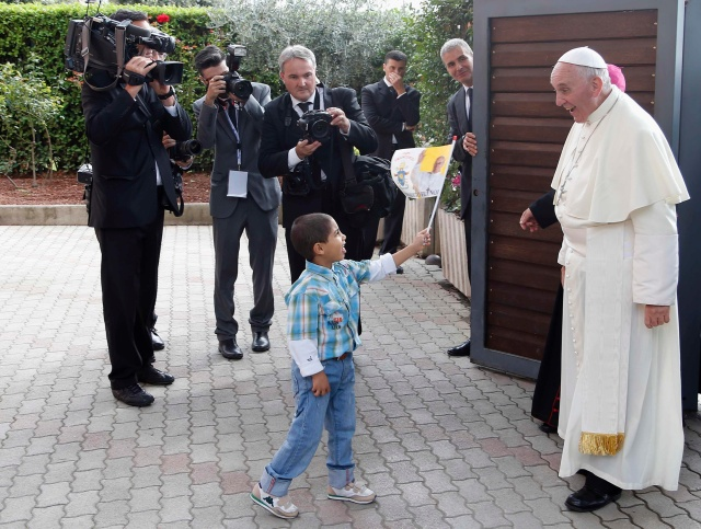 Child waves a flag as Pope Francis arrives at the Caritas residence in the Italian pilgrimage town of Assisi