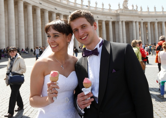 Newly married couple enjoys ice cream cones after pope's general audience in St. Peter's Square at Vatican