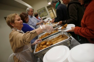 Volunteers serve people during free dinner provided by Chicago Catholic Charities