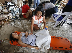 Woman comforts pregnant relative at makeshift birthing clinic after super typhoon hits Philippines