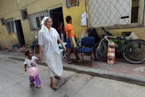 COMBONI NUN WHO WORKS WITH REFUGEES WALKS WITH CHILD IN FRONT OF SHELTER IN TEL AVIV