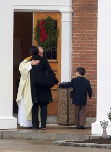 2012 photo of Newtown pastor receiving mourners for funeral of young victim of school massacre
