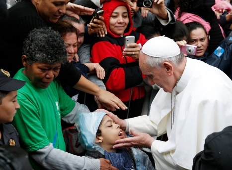 Pope Francis blesses boy during visit to slum complex in Brazil