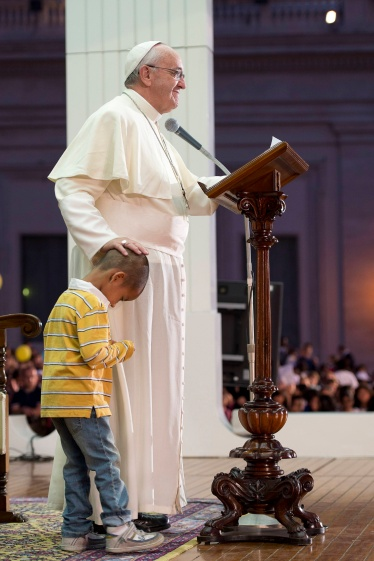Pope Francis touches the head of a child during special event for families in St. Peter's Square