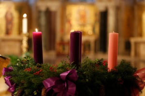 Lit candle seen on Advent wreath during Mass in Crypt Church at national shrine in Washington