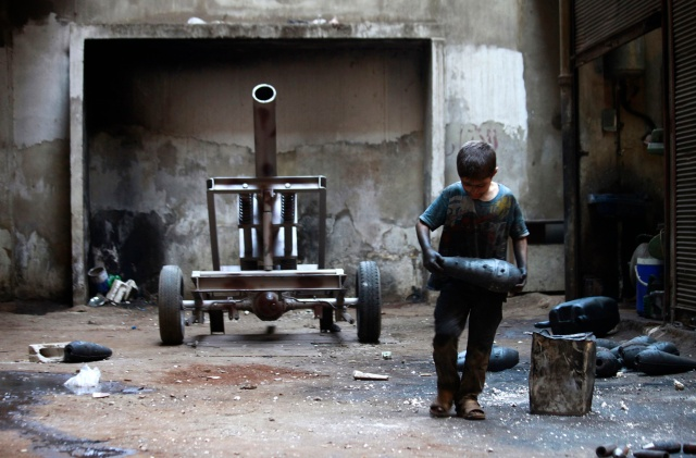 Boy carries mortar shell in weapons factory of Free Syrian Army in Aleppo