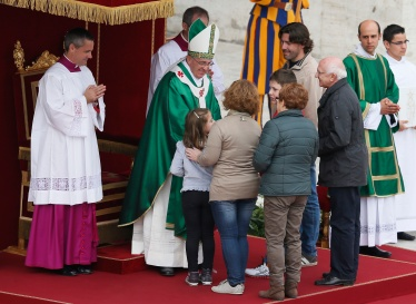 Pope greets family as they present offertory gifts during Mass for families in St. Peter's Square at Vatican