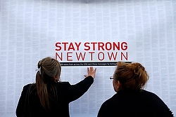 Woman touches sign at Newton, Conn., memorial (CNS photo from Reuters)