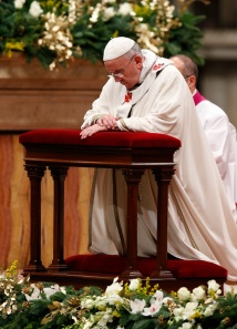 Pope kneels in prayer as he celebrates Christmas Eve Mass in St. Peter's Basilica at Vatican